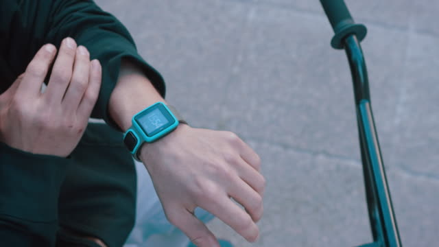 BMX biker looking at his smartwatch