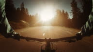POV Biker riding his bike on a country road into sunset