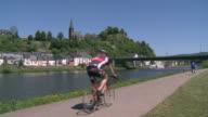 WS  Bikers biking  with river Saar and castle ruin / Saarburg, Saar-Valley, Rhineland-Palatinate, Germany