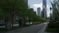 Bikers on bike path in lower Manhattan with tilt up to downtown NYC skyline