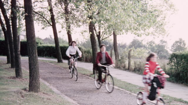 1974 MONTAGE Bikers riding on bicycles down a park path and on hilly terrain / United Kingdom