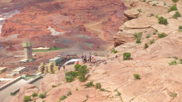 WS AERIAL DS ZI bikers taking group photo at edge of cliff / Moab, Utah, United States