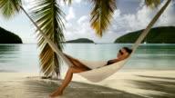 bikini Frau schlummern in einer Hängematte am Strand am Karibischen Meer