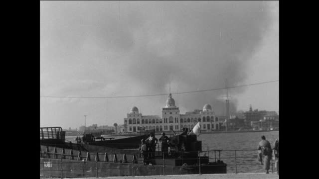 Billowing smoke and the aftermath of exploding ammunition throughout Port Said / Egypt/ Suez Canal crisis