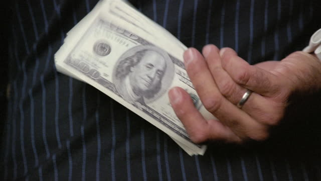 US$100 bills exchanging hands behind man's back