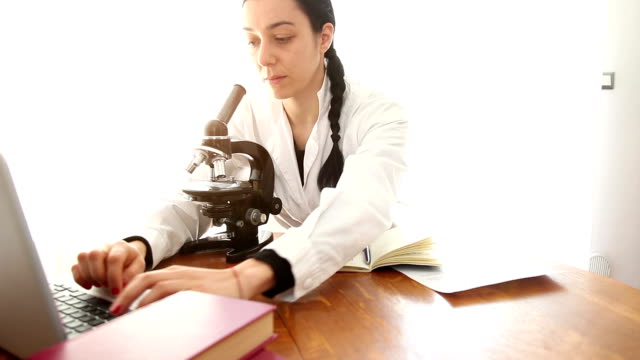 Biologist analyzing using microscope