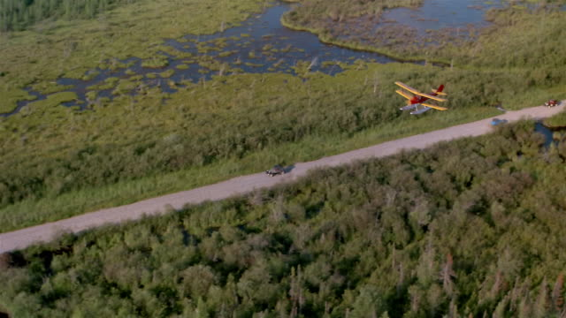 AIR TO AIR, Biplane flying over country road, Canada