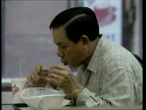 Bird slaughter ITN Dr Lo Wing Lok intvwd drastic action was needed sooner rather than later Men eating fried chicken in restaurant CMS mechanical...