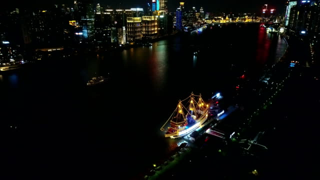bird view of shanghai huangpu rive with lighted trourism vessel parking at the dock