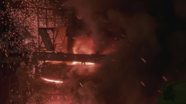 Bird's eye shot of workers in a fiery foundry or factory with sparks and molten steel.