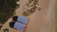 Bird's eye view of Brighton beach with 2 women waving at the camera