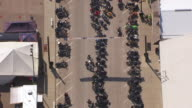 MS AERIAL Birds Eye View of over rows of parking motorcycles in downtown street / Sturgis, South Dakota, United States