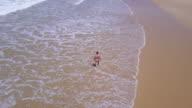 Bird's eye view tracking shot of a woman at the beach, Apollo Bay, Great Ocean Road, Victoria, Australia