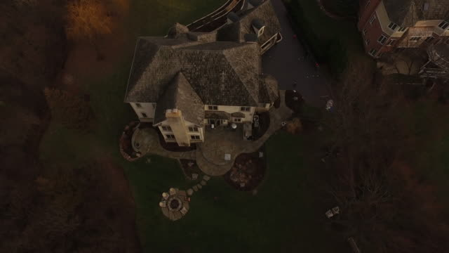 Bird's eye view zooming in on large white house in Chicago suburb