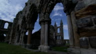 Birds fly over the arched ruined walls and towers of the Cathedral St Andrew in Scotland. Available in HD.
