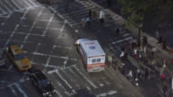 Birds-eye-view of an ambulance trying to turn at a busy crosswalk.