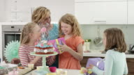 birthday child blows out candles and receives presents