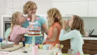 birthday child has blown out candles on cake together with mother and friends