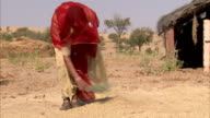 A Bishnoi woman spreads seeds on the sandy ground. Available in HD.