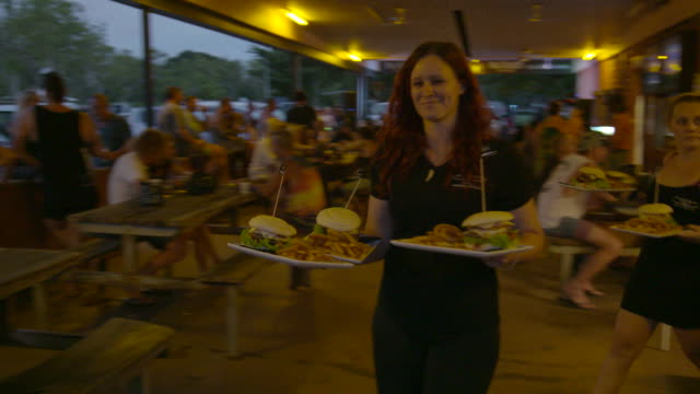bistro waitresses bring crocodile and buffalo burgers and chips meals out to table in outdoor beer garden various pub patrons eating burgers