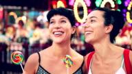 Bite a lollipop at amusement park in Coney Island