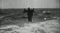 Black and white 1914 composite wide shot Jesus rising from water and walking on surface / praying as waves crash