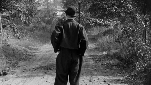 Black and white 1917 medium shot Larry Semon walking and turning his empty pockets inside out in