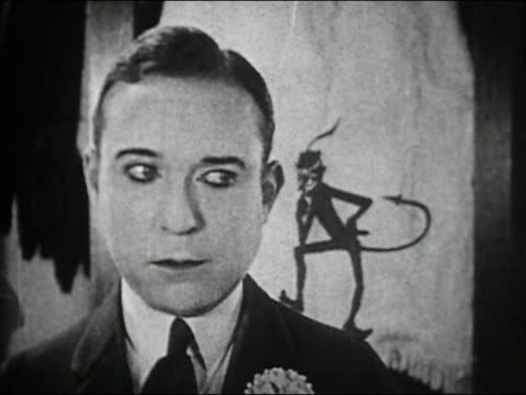 Black and white 1924 close up cartoon devil whispering into Harry Langdon's ear / 'Picking Peaches'