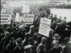 Black and white 1930s high angle pan crowd at Great Depression labor rally holding placards and marching / AUDIO