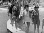 Black and white 1940 tilt up line of women in swimsuits walk on walkway over water in contest / Coney Island, NY