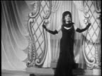 Black and white 1943 dolly shot from big band to Powers models modeling evening dresses / feature /AUDIO