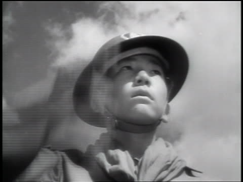 Black and white 1943 low angle close up Japanese-American Boy Scout in helmet saluting outdoors / documentary /AUDIO