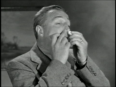 Black and white 1945 close up man inhaling nasal spray into both nostrils / AUDIO
