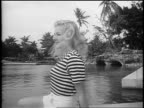 Black and white 1948 blonde model in striped shirt standing by swimming pool outdoors / Coral Gables, FL /AUDIO