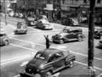 Black and white 1948 high angle policeman stops traffic at intersection so boy can cross street / Milford, CT / edu