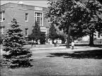 Black and white 1948 long shot children entering school building / Milford, CT / educational /AUDIO