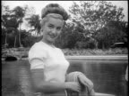 Black and white 1948 model in sweater smiling at camera outdoors / Coral Gables, FL / newsreel /AUDIO