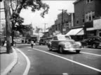 Black and white 1948 pan boy runs across small town street to sidewalk and stops / Milford, CT / educational AUDIO