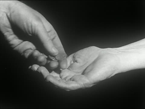 Black and white 1963 close up hand dropping coins into another person's palm / AUDIO
