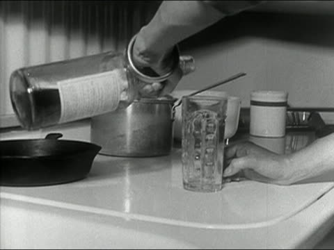 Black and white 1963 close up housewife pouring drink from bottle on kitchen counter / AUDIO