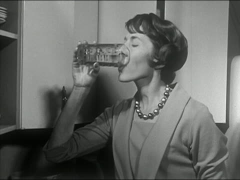 Black and white 1963 medium shot housewife drinking and smoking in kitchen / AUDIO