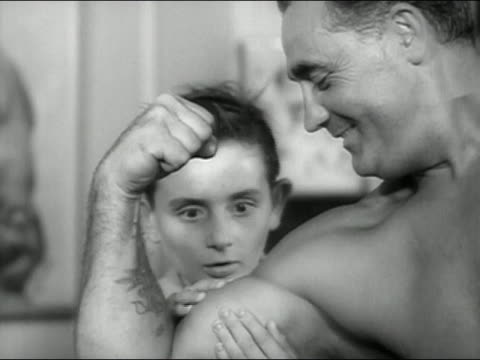 1946 black and white Charles Atlas flexing bicep / astonished boy feeling muscle / astonished man feeling muscle