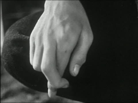 1955 black and white close up hand resting on leg with index and middle fingers crossed