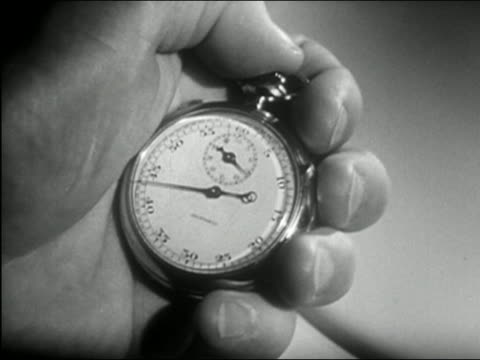 1950 black and white close up man's hands holding ticking stopwatch / pressing the stopper with thumb