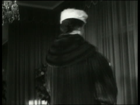 Black and white close up of woman modeling hat and coat in fashion show /Italy / NO