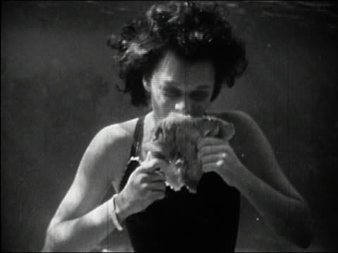 1946 black and white close up woman taking bite of turkey leg at underwater Thanksgiving dinner