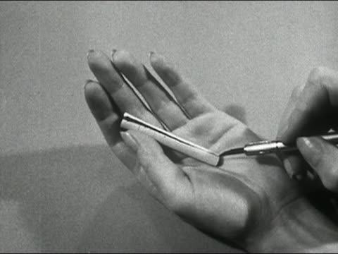 1950 black and white hands slicing cigarette down middle with razor (quality-control inspection) / zoom in tobacco