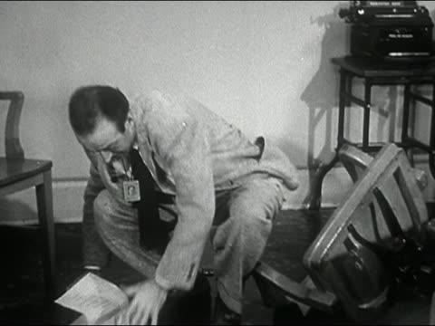 1944 black and white man reading file at desk / leaning back in chair and falling over / getting back in chair