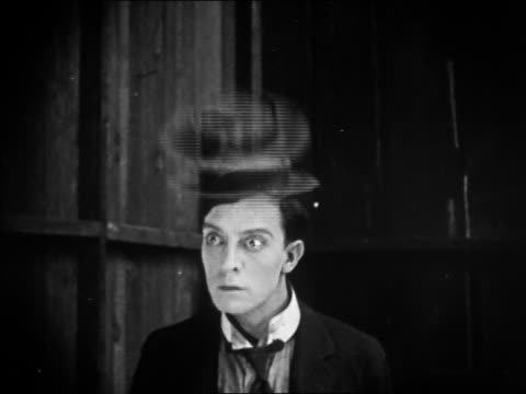 1922 black and white medium shot Buster Keaton's hat flipping to register his surprise / 'The Blacksmith'