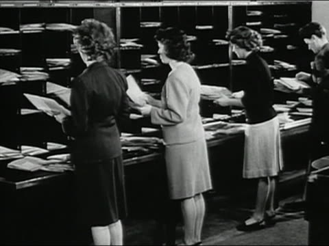 1947 black and white medium shot four female office workers sorting papers and mail / AUDIO